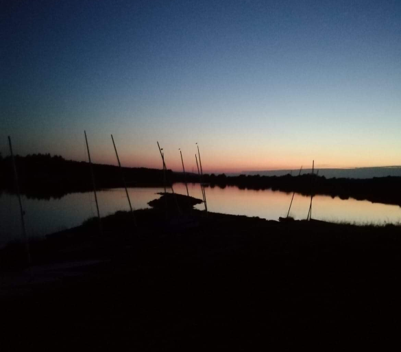 View over the spit, with the loch dead calm. Sunset has well started.
