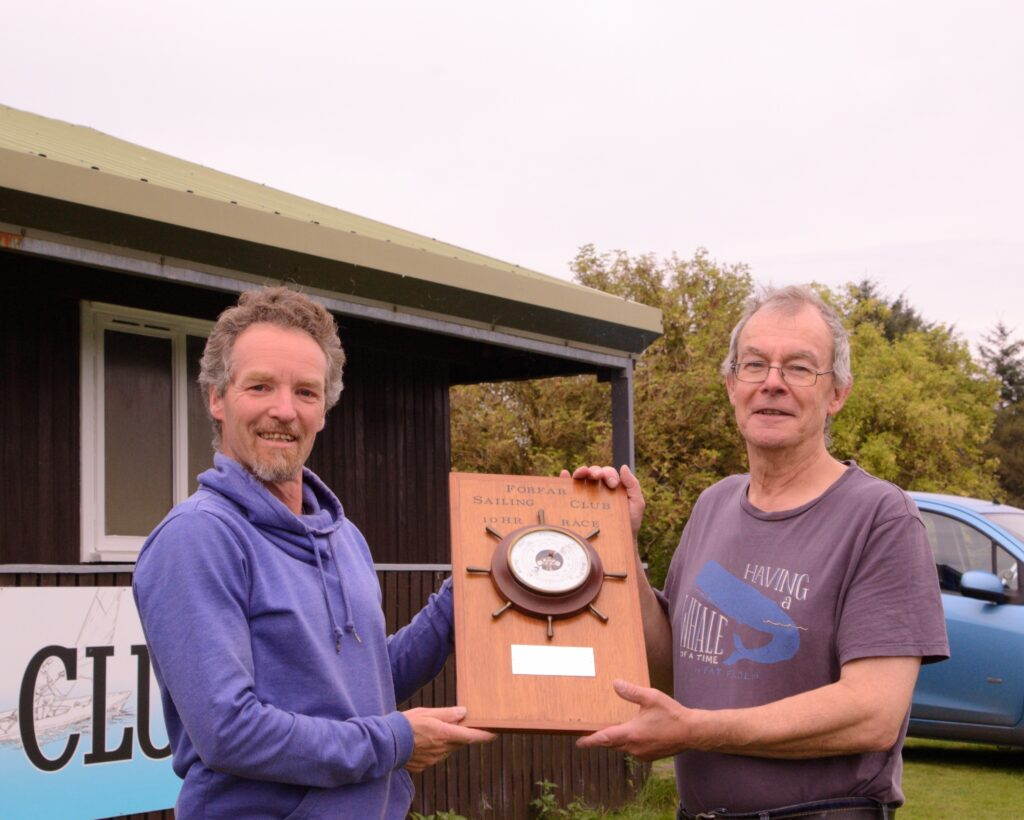 Erwin and David holding the trophy (a board with a barometer surrounded with a boat steering wheel 'helm')
